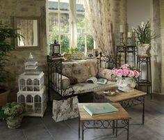 Canapé en fer forgé de chez Comptoir de famille - Avec une cage d'oiseau blanche, un vase en céramique, une petite lanterne, miroir, des grandes bougies, des rideaux et une petite table basse de salon.