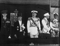 Crown Prince Michael of Romania, later HM King Michael I (first at left), HM Carol II of Romania (center) and HRH Prince Nicolae, the King's brother (right) at a military parade. The Royal Coat of Arms of Romania (small variant) can be seen behind. ROMANIANS ASK FOR THEIR MONARCHY BACK! https://www.facebook.com/anrmro