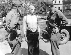 Maj. Fulton Vowell and Capt. Herschel Auerbach (right) apprehend an SS guard, assistant warden at the Berga concentration camp. When American troops entered the camp, he fled to an old woman's home, but was betrayed by German civilians and taken into custody.