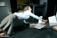 Stock Photo : Young woman tripping in office with paperwork, side view