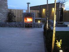 Verlichting van in-lite en een steenkorf met open haard zorgen voor heel wat sfeer in de tuin.