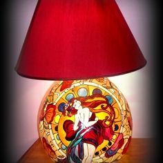 La01 Sole Lampada dipinta a mano  Lampada dipinta a mano in trasparenza con doppia luce interna (una diretta verso l'interno della base in vetro e l'altra verso il paralume). Il dipinto riprende una versione della GIUNCHIGLIA di Alphonse Mucha, interpretato da Hanùl. La lampada è poi impreziosita da un delizioso paralume rosso in pendant col dipinto. Effetto ottico e giochi di luce sulle pareti garantiscono una suggestione senza eguali.  Per avere informazioni su come ricevere una lampada…