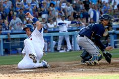A.J. Ellis #17 of the Los Angeles Dodgers slides home to score a run past catcher Jose Lobaton #59 of the Tampa Bay Rays on a two run single by pitcher Clayton Kershaw in the second inning at Dodger Stadium on August 11, 2013 in Los Angeles, California. (credit: Stephen Dunn/Getty Images)