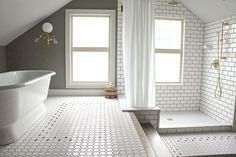 KAEMINGK DESIGN:  Two level period attic bathroom with subway tile and brass.
