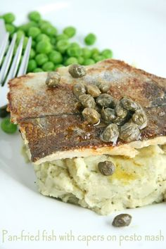 An easy dinner party dish of pan-fried fish fillets on pesto mash with capers. You can use any firm white fish fillets like hake or cod.