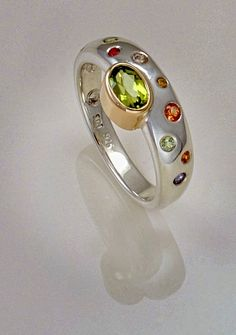 Ring offset with peridot in 9ct yelow gold on sterling silver band flush set with sapphires.