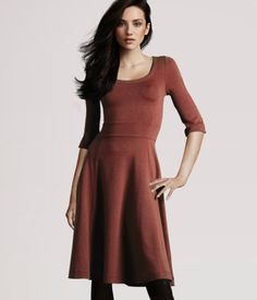 Thick jersey dress with a fitted bodice and 3/4-length sleeves. Gently flared skirt falls just above the knee.