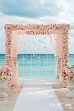 Overlooking the turquoise Bahamian waters, a pink and white arbor covered in flowers drips with crystal strands and glass bubbles filled with flower petals. Check out our Wedding Altar gallery: http://www.colincowieweddings.com/the-galleries/wedding-decor/wedding-altar