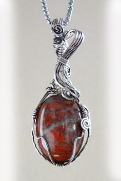 This gorgeous Indian River jasper pendant has a deep orange rust color with black and crystal inclusions. It is wire wrapped in solid sterling silver which has been antiqued and sealed. The pendant is artistically sculpted with a large bail and a sweeping silver ribbon. One-of-a-kind. Handmade. Free US shipping.