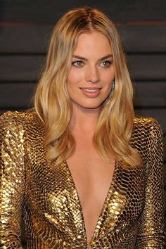 Margot Robbie fashioned a gold Oscar-Inspired gown by Diane von Furstenberg as she stopped and posed for pictures at the Vanity Fair after-party in Beverly Hills. The dress featured a metallic sequined fabric with a snakeskin-like texture. Margot