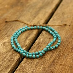 Fair Trade Teal Beaded Wakami Bracelet — Handmade in Guatemala — from Fair & Square Imports — This adjustable slip knot bracelet features copper and glass turquoise-colored beads on a waxed thread.