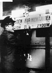 A Krakow streetcar worker installing a sign separating Jewish and non-Jewish passengers. The sign, in German and Polish, indicates with arrows that Jews go to the left, non - Jews to the right.