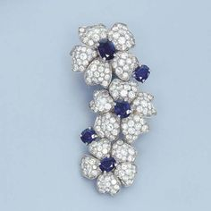 A SAPPHIRE AND DIAMOND FLORAL CLIP, BY CARTIER Designed as three cascading flowerheads with oval-cut sapphires and pavé-set diamond petals to the sapphire collet detail, circa 1935, with French import mark for platinum Signed Cartier