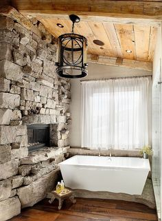 02-AD-Ski-lodge-inspired-rustic-bathroom-with-a-stone-wall-and-sheer-curtains