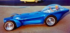 """Ed Roth inside his """"Orbitron"""" custom car, an asymmetrical design created in 1964. Orbitron featured three primary colored headlights, which in theory when illuminated concurrently would blend into a white beam."""