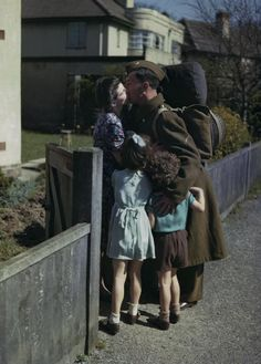 Lance Bombardier Jack Grundy of the Royal Artillery embraces his wife Dorothy and children Randall and Gilda at his home in Irby in Cheshire, at the start of seven days leave, 14 April 1944 ~