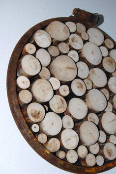 fashioned from a recycled steel military drum seal embellished with varying sizes of reclaimed and sliced aspen branches.