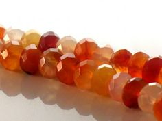 DESIGNER CARNELIAN FACETED RONDELLE BEADS. 8MM. AAA QUALITY.  Carnelian Faceted Rondelle beads measuring approximately 8mm in size exhibiting a vitreous luster, transparent glow, in colors ranging from clear to yellow, vibrant orange and cherry red with no eye visible inclusions, slight natural swirling, beautiful facets, and exceptional polish.