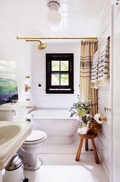 the perfect little bathroom. love that small wooden stool, all white, and touches of brass.