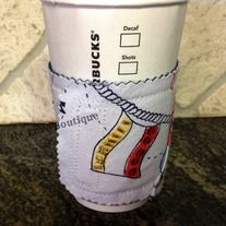 """This adorable and functional coffee """"cozy"""" is one of a kind!  Recycling the cardboard sleeve from a local coffee shop, it is sandwiched in between a piece of denim and fabric that was part of a ladies capri jacket. (Matches our """"Down by the Seashore"""" tote bag)  Wraps around securely with Velcro..."""