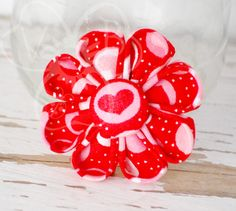 """This flower won't wilt or fade! Wear it on Valentine's Day or give it to your love as a gift.  """"Warm My Heart"""" is a sweet daisy style kanzashi flower in red fabric with white and pink heart print, with a handmade fabric button center.  This hair accessory is secured to an alligator clip for ea..."""