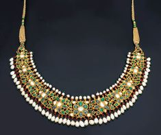 A MODERN DIAMOND, GEM-SET AND ENAMEL NECKLACE Designed as openwork foliate clusters set with cabochon emeralds and table-cut diamonds within foiled foliate surrounds suspending a freshwater pearl fringe, the polychrome enamelled reverse depicting foliate motifs, North Indian, contemporary, 32.0cm long