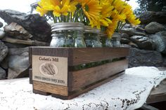 "Handmade wood crate with or without vintage label, includes 4 mason jar vases with handmade flower frog tops, for easy floral displays! ( Daisies not included) These lids make for easy DIY floral dislays. These crates are perfect for any primitive country decor, or great for weddings and parties!  Crate measures 14"" L x 4"" W x 4"" H. Wood is stained a dark brown."