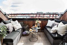 aménagement toit terrasse avec deux canapés en résine tressé, deux tables d'appoint en laiton et un tapis extérieur
