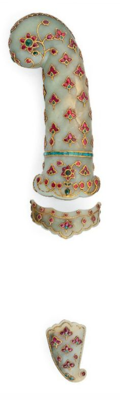 A GEM-SET JADE HILT AND TWO SCABBARD MOUNTS   INDIA, 19TH CENTURY OR LATER   The hilt of pistol shape with rounded quillons, the two scabbard mounts of typical shape, the gold inlaid decoration with a lattice of trefoil palmettes set with foiled rubies overall, a long palmette along the pommel, the hilt inlaid with a band of emeralds above the quillon, minor loss to hilt, small restoration to the upper scabbard mount