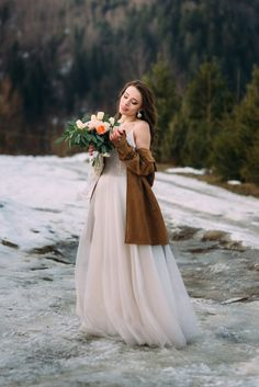 Bride in a wedding dress enjoys a bouquet of flowers. wonderful winter wedding photo shoot. Download it at freepik.com! #Freepik #photo #background #wedding #winter #snow