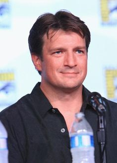 """Nathan Fillion at the """"Firefly"""" 10th Anniversary Reunion panel at San Diego Comic-Con International 2012. Met with a ballroom packed with 10,000 people, the cast an crew reminisced about the show and assured fans that ten years later, the """"Firefly"""" 'verse is far from dead. Keep flying, Browncoats! http://www.examiner.com/article/nathan-fillion-and-firefly-alum-attend-10th-anniversary-panel-at-sdcc-2012"""