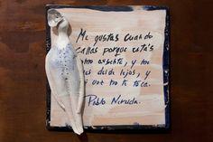 Azulejo con poema de Pablo Neruda y figura de mujer.