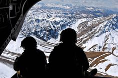 U.S. soldiers watch from the rear ramp of a CH-47 Chinook helicopter while flying over the mountains in the Khas Uruzgan district of Afghanistan's Uruzgan province