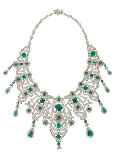 A BELLE EPOQUE EMERALD AND DIAMOND BIB NECKLACE, CIRCA 1910. Of foliate scrolling design, set throughout with old-cut diamonds and variously-cut emeralds, mounted in silver and gold.
