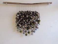 felted balls... millions of 'em... hanging from a branch. Gorgeous-Cool!