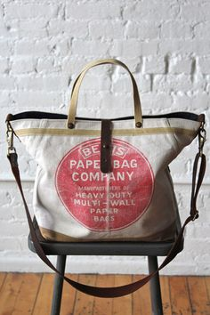 Sturdy, worn-in canvas salvaged from a 1940's era Bemis Paper Co. work apron has been detailed with 1940's era cotton webbing and turned into a perfect weekender.