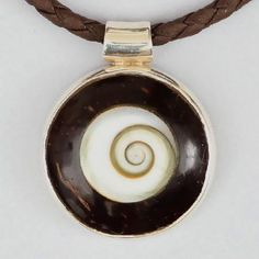 Coconut And Silver Spiral Pendant - Tribal Jewelry - Tribal Spiral Jewelry - Shiva Eye Jewelry - Wood Jewelry - Carved Wooden Spiral  Small and round coconut pendant set with shiva-eye and silver.  Beautiful chocolate shiny color.  Pendant Size: 22mm.  Don't forget to choose the pendant size and which leather chain you like to add to the pendant.  $33