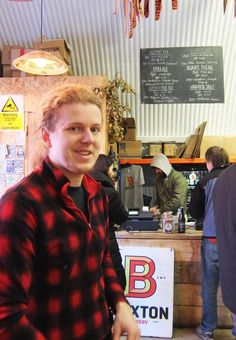 Sam at Brixton Brewery - bar and beer list above iin background.