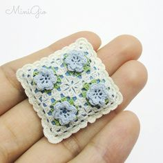 One miniature crochet pillow in cream with little blue flowers and green leaves, you can see the back of the pillow in the last photo. Stuffed with