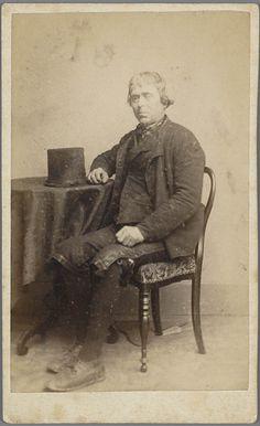 Man in Walcherse streekdracht. De man draagt een kuitbroek. op het tafeltje ligt een 'tunhoed'. 1875-1890 #Zeeland #Walcheren