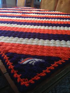 DENVER BRONCOS AFGHAN in RH Soft Navy, Soft White, Tangerine  MADE BY GLENDA TAYLOR    SIMPLE BORDER:    row 1 in tangerine do sc ch 2 between each block of 3 stitches, doing sc ch2 twice in each corner row 2 in tangerine do same as row 1 row 3 in navy same as row 1