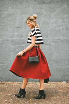 Striped crop top in black and white, red knee length skirt, black ankle boots, and a Chanel strap purse.