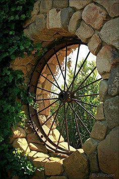 wagon wheel window in garden stone wall