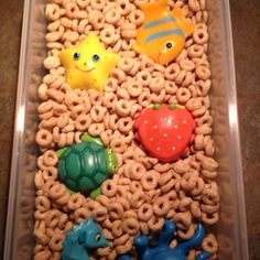 Cheerio sensory bin to play with food texture.  Visit pinterest.com/arktherapeutic for more #sensoryplay and #feedingtherapy ideas