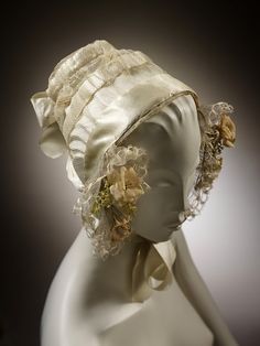 1840-1845 Woman's cap, possibly for a wedding, made from wide cream silk satin ribbon and net, tied under the chin with satin ribbon. The cap is trimmed with bands of eau de nile, satin ribbon and strings of the same. It is scuttle shaped, curving foward to cover the ears where it is trimmed with blonde lace and small clumps of artificial flowers made of silk