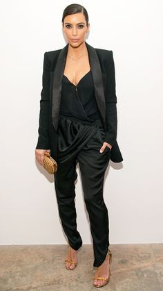 """For a press event in Los Angeles, Kardashian looked elegant in black silk pants, a black blouse, and a black blazer. She added some sparkle to the look with gold sandals, a gold clutch, and her gold Jennifer Meyer """"Nori"""" necklace."""