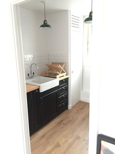 Ikea Laxarby cabinets, single bowl Domsjo sink, pale wood counters, white subway tile backsplash, black pendant light.