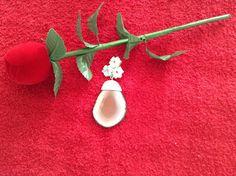 Em ágata com flores em madreperola tendo no centro granadas naturais.