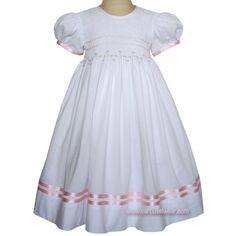 Thisξprecious, white 100% cotton girls heirloom smocked dress has hand embroidered pink rosebuds across the smocked bodice. The sleeves and skirt are trimmed with pink satin ribbon and entredeux givin