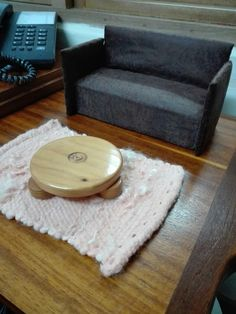 Diy Barbie couch. Found an old coaster to use as a coffee table.